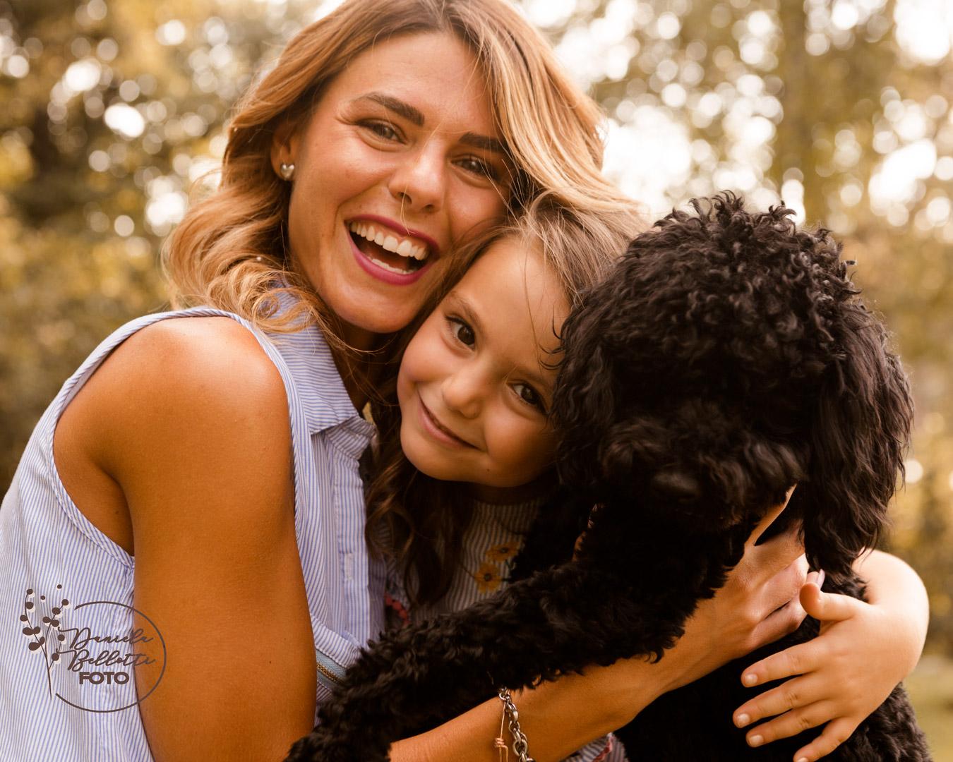 mamma e bimba abbracciate con barboncino nero in mezzo