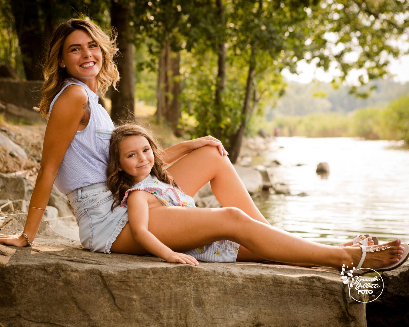 mamma e bimba sedute in riva al lago