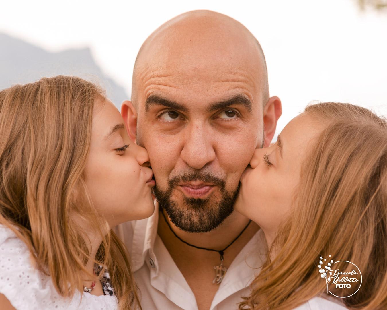 papa e bimbe a lato che gli danno un bacio