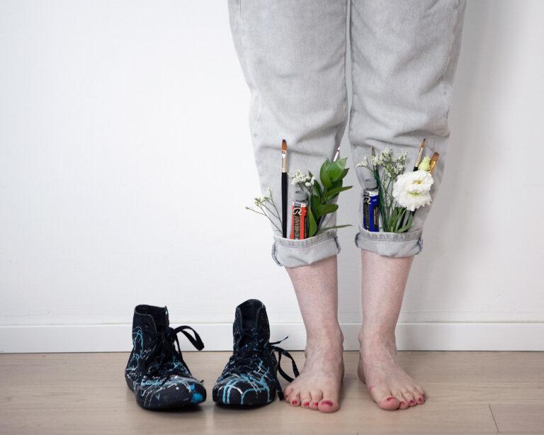 artista con pennelli nei risvolti dei pantaloni