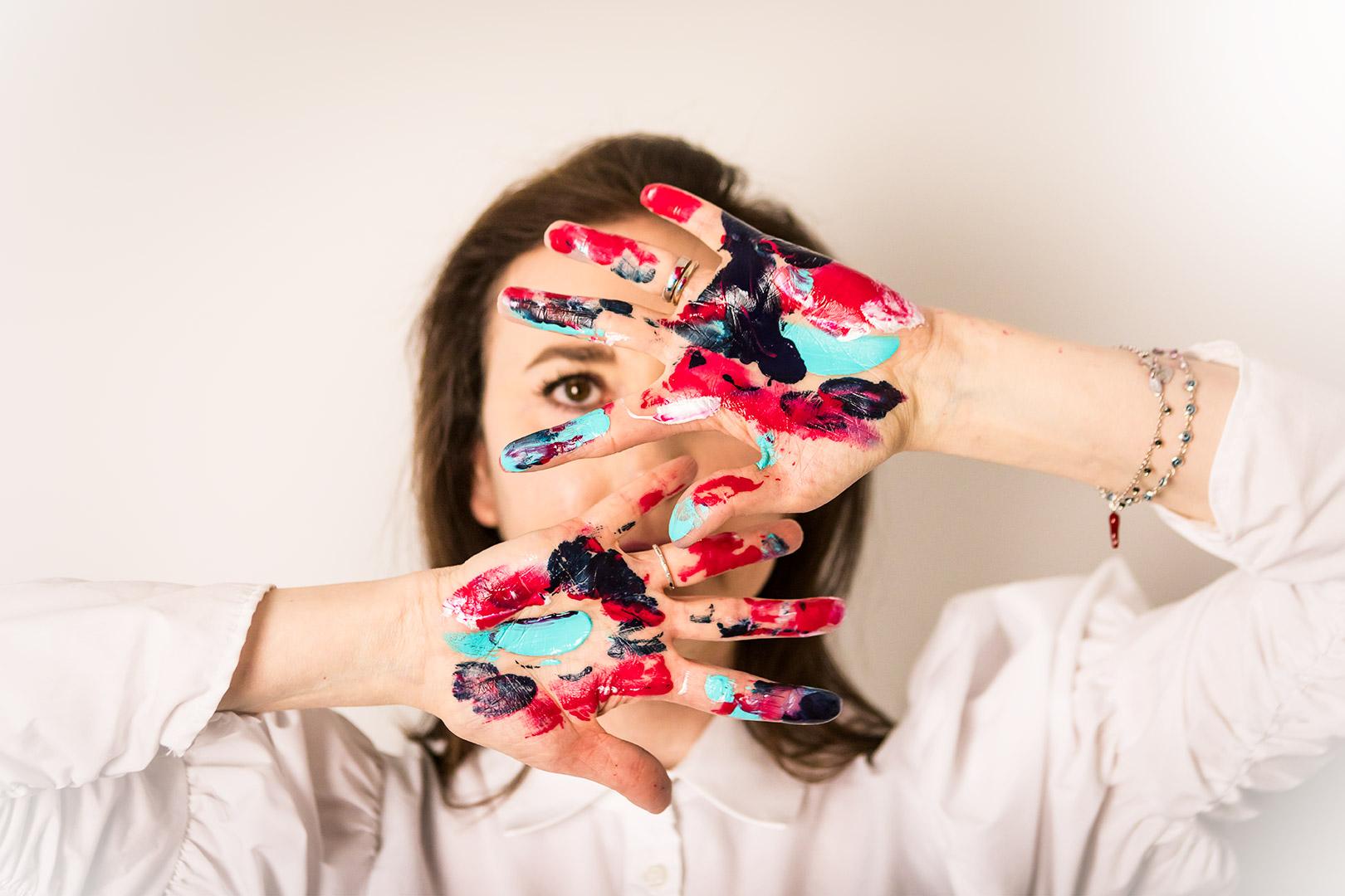 artista con mani colorate di vernice