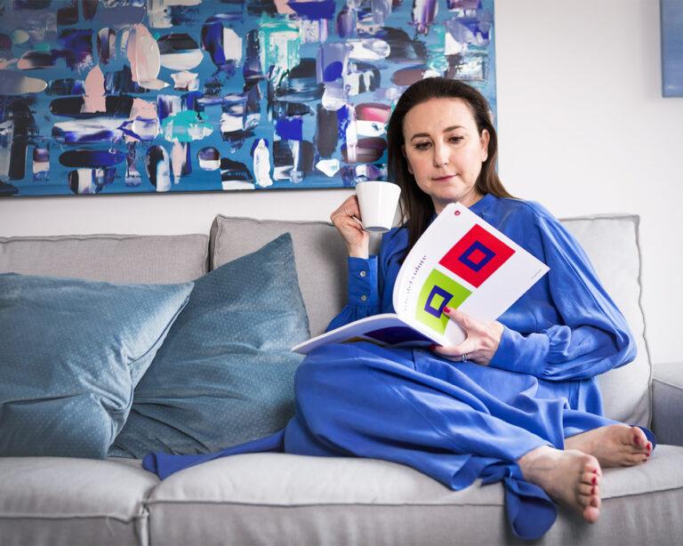 donna sul divano che legge una rivista