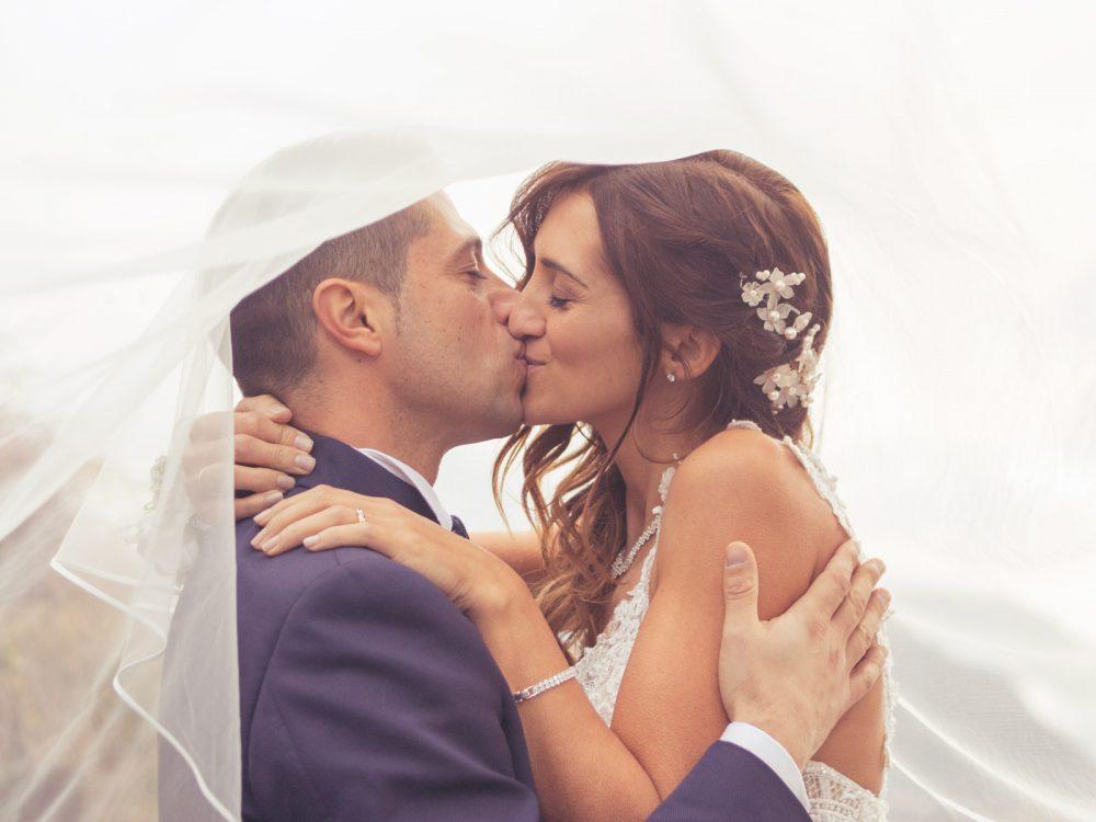 sposi-che-si-baciano-sotto-il-velo